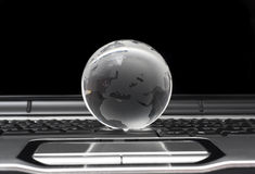 Glass globe on laptop Stock Image