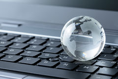 Glass globe on laptop keyboard Stock Photo