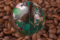 Glass globe lying on the coffee beans Royalty Free Stock Photo