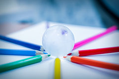 Glass globe lying and colored pencils - bussines Stock Photography