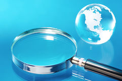 Glass globe and magnifying glass. Glass globe and magnifying glass on blue background royalty free stock photography
