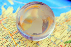 Glass globe and map. The glass sphere of a terrestrial planet lies on a map Stock Images