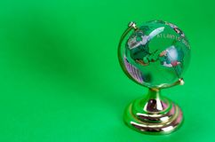 Glass globe with marked continents on a green background stock photo