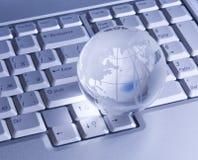 Glass Globe On Keyboard Stock Photo