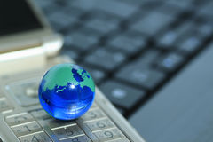 Glass globe over cellphone Stock Photos