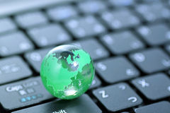 Glass globe over keyboard Royalty Free Stock Photography