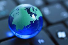 Glass globe over keyboard Royalty Free Stock Photos