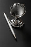 Glass globe and pen Stock Images