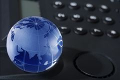Glass globe with phone Royalty Free Stock Photos