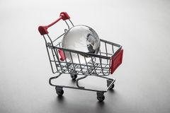 Glass globe in the shopping trolley concept Stock Photos