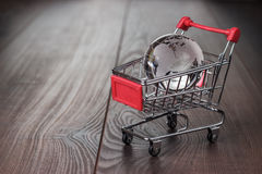 Glass globe in the shopping trolley concept. Glass globe in the shopping trolley global market concept Royalty Free Stock Image