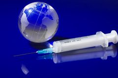 Glass globe with a syringe Stock Images