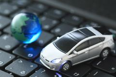Glass globe and   toy car over keyboard Royalty Free Stock Photo