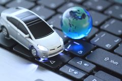 Glass globe and   toy car over keyboard Royalty Free Stock Photography