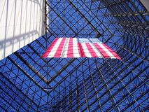 Glass and Glory. Inside shot of the John F. Kennedy Presidential Library and Museum (aka the JFK center) in Boston, Massachussetts.  Large American flag hangs in Stock Photos
