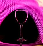 Glass goblet on a black background with pink backlight color. stock image