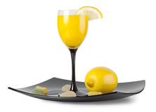 Glass goblet with the juice. And lemon on a plate Stock Photos