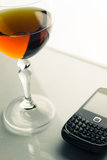 Glass goblet & mobile phone Stock Photography
