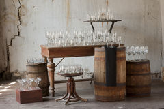 Glass goblets. Empty glass glasses stand in rows on the drums, tables, stools and boxes Royalty Free Stock Photography