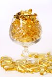 Glass with gold boluses. Glass with gold shiny boluses Royalty Free Stock Photos