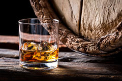 Glass of good brendy with ice in the distillery basement. On wooden background royalty free stock image