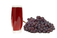 A glass of grape juice with a cluster of grapes Royalty Free Stock Photography