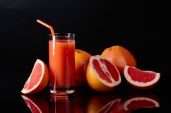 Glass of  grapefruit juice and cut fruits on black background. Stock Photo