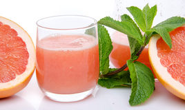 Glass of grapefruit juice with fresh grapefruits and mint Stock Image
