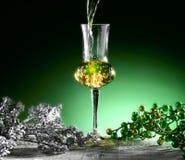 Glass of grappa. Poured, Christmas theme Royalty Free Stock Photos