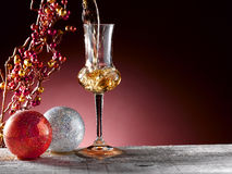 Glass of grappa. Poured, Christmas theme Royalty Free Stock Image