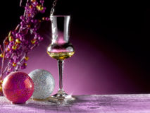 Glass of grappa poured. Christmas theme Royalty Free Stock Images