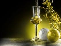 Glass of grappa poured. Christmas theme Royalty Free Stock Photography