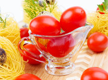 Glass Gravy boat with cherry tomatoes. Stock Photos