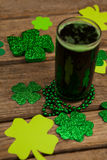 Glass of green beer, beads and shamrock for St Patricks Day Royalty Free Stock Photography