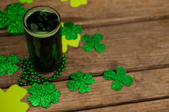 Glass of green beer, beads and shamrock for St Patricks Day Royalty Free Stock Images