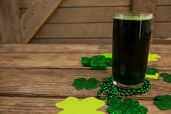 Glass of green beer, beads and shamrock for St Patricks Day Stock Images