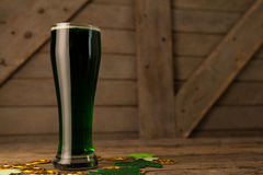 Glass of green beer, chocolate gold coins and shamrock for St Patricks Day Royalty Free Stock Image