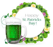 Glass of green beer with coins and clover Stock Images