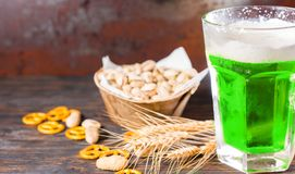 Glass with green beer and a head of foam near plate with pistach. Ios, wheat, scattered small pretzels and peanuts on dark desk. Food and beverages concept Royalty Free Stock Image