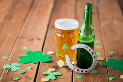 Glass of green beer, horseshoe and gold coins Stock Photo