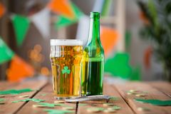 Glass of green beer, horseshoe and gold coins Royalty Free Stock Images
