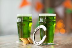 Glass of green beer, horseshoe and gold coins Royalty Free Stock Photos