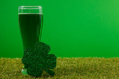 Glass of green beer and shamrock for St Patricks Day on grass Royalty Free Stock Image