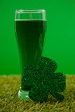 Glass of green beer and shamrock for St Patricks Day on grass Royalty Free Stock Images