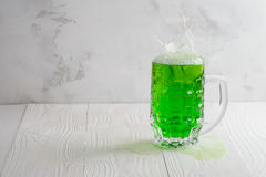 Glass of green beer with splash Royalty Free Stock Images
