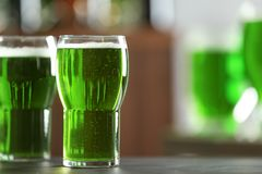 Glass of green beer on table in bar. Saint Patrick`s day celebration Royalty Free Stock Photos