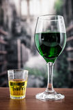 Glass with green cocktail and yellow shot Royalty Free Stock Images