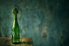 Glass green empty bottle. On dark background with candy stock images