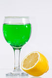 The glass of green liquor and lemon. The glass of transparent green liquor and lemon Royalty Free Stock Photos