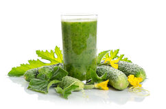 Glass with green smoothie and cucumbers, flowers, leaves Royalty Free Stock Photography
